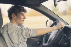 Le jeune adolescent apprend comment conduire la voiture f image stock