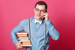 Le jeune adolescent masculin avec des expressions du visage agréables, garde la grande pile de livres, parle du téléphone, se pré photographie stock