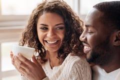 Le jeune Afro-américain de sourire couplent le thé potable dans le café image stock