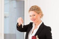 Le jeune agent immobilier est avec des clés dans un appartement Image stock