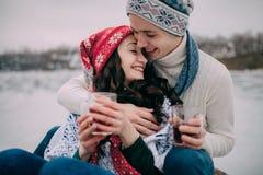 Le jeune ajouter aux tasses de thé chaud dans leurs mains est se reposant et souriant pendant la promenade d'hiver closeup Images stock