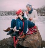 Le jeune ajouter aux tasses de thé chaud dans leurs mains se repose à la roche et rit pendant la promenade d'hiver Photo libre de droits