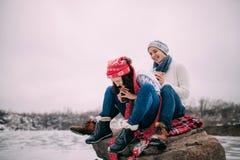Le jeune ajouter aux tasses de thé chaud dans leurs mains se repose à la roche et rit pendant la promenade d'hiver Photo stock