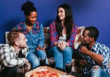 Le jeune ami s'asseyent sur le divan à la maison avec la pizza fraîche Image libre de droits