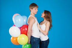 Le jeune amour de sourire couplent tenir des ballons dans le studio Image libre de droits
