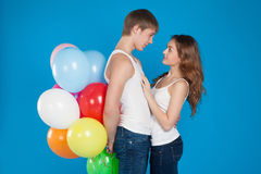 Le jeune amour de sourire couplent tenir des ballons dans le studio Photographie stock libre de droits