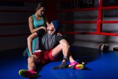 Le jeune appui sportif de femme et étreignent son ami dans un r de boxe Photo stock