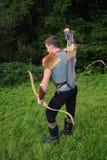 Le jeune archer médiéval avec la chemise à chaînes atteint pour la flèche, avec l'arc à disposition Images libres de droits