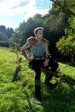Le jeune archer médiéval avec la chemise à chaînes s'assied sur la branche dans la nature à la lumière du soleil, klaxon de boiss Images libres de droits