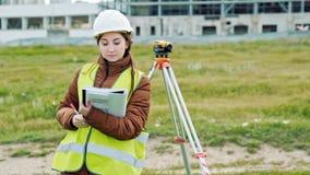 Le jeune arpenteur smileing de femme dans les vêtements et le casque de travail verts ajuste l'équipement, produit des calculs et banque de vidéos