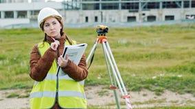 Le jeune arpenteur smileing de femme dans les vêtements et le casque de travail verts ajuste l'équipement, produit des calculs et clips vidéos