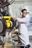 Le jeune artisan utilisant la vitesse protectrice tout en employant la circulaire a vu image stock