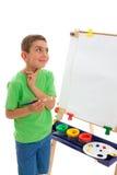 Le jeune artiste contemple ce qui peignent images stock