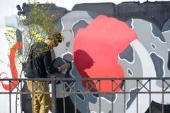 Le jeune artiste dessine un pulvérisateur de graffiti sur un mur Image libre de droits