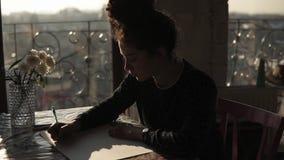 Le jeune artiste féminin mignon avec les cheveux bouclés a tiré dedans un petit pain, se reposant par la table et dessinant avec  banque de vidéos