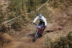 Le jeune athlète de cavalier sur la bicyclette monte le long d'une traînée poussiéreuse Images stock