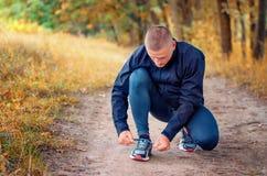 Le jeune athlète de forme physique dans un noir folâtre les leggins et le lien d'espadrilles photographie stock