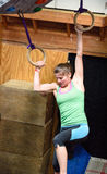Le jeune athlète féminin regarde vers le bas pendant qu'elle balancent d'un anneau à l'autre Photographie stock libre de droits