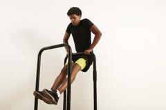 Le jeune athlète noir faisant le poids du corps rame sur les barres mobiles photographie stock libre de droits