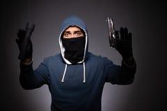 Le jeune bandit dans le capot sur le fond gris image libre de droits