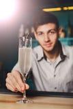 Le jeune barman offre le verre de champagne dans la barre de boîte de nuit Photo libre de droits
