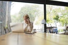 Le jeune beau concepteur blond de fille boit du thé dans le courrier de restaurant et de contrôle sur votre ordinateur portable Photos stock