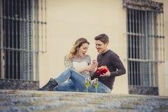 Le jeune beau couple dans l'amour célébrant le jour de valentines présente et pain grillé Photo stock