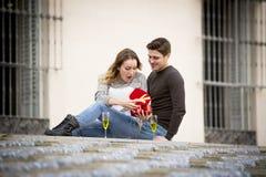 Le jeune beau couple dans l'amour célébrant le jour de valentines présente et pain grillé Images stock