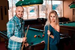 Le jeune beau couple gentil joue le billard et le sourire sur l'appareil-photo Photo libre de droits