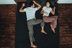Le jeune beau couple se trouve sur le lit image stock