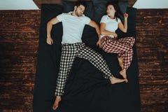 Le jeune beau couple se trouve sur le lit photos libres de droits