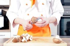 Le jeune beau cuisinier féminin fait cuire dans une cuisine de la nourriture avec de la viande de légumes Photos stock