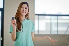 Le jeune beau docteur féminin de sourire heureux montrant l'AR vide Photo libre de droits