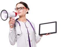 Le jeune beau docteur féminin tenant le comprimé dans des ses mains parlent dans le mégaphone sur le fond blanc photo stock