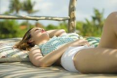 Le jeune beau et sexy mensonge coréen asiatique de femme confortable au lit pliant de jardin de station de vacances de vacances a photo stock
