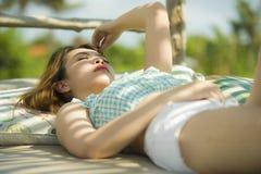 Le jeune beau et sexy mensonge coréen asiatique de femme confortable au lit pliant de jardin de station de vacances de vacances a photographie stock