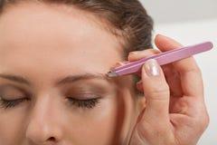 Le jeune beau sourcil de femme plumant des brucelles observe des cheveux photographie stock libre de droits