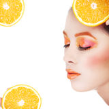 Le jeune beau visage de femme avec l'orange composent Photos stock