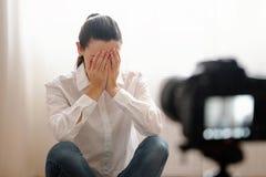 Le jeune blogger féminin avec le dslr de caméra vlogging a soumis à une contrainte avec des bras couvrant le travail en ligne mod photos libres de droits