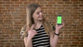 Le jeune blonda heureux montre l'écran vert du smartphone, point dans lui, concept de communication, fond de brique banque de vidéos