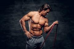 Le jeune bodybuilder puissant fait des exercices avec le caoutchouc photos libres de droits