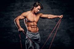 Le jeune bodybuilder puissant fait des exercices avec le caoutchouc image stock