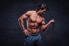 Le jeune bodybuilder puissant fait des exercices avec le caoutchouc photo stock