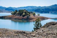 Le jeune bois du pin sur le fond éloigné d'île chez l'Aoos jaillit lac dans le Metsovo dans Épire Image stock