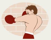 Le jeune boxeur dans des shorts rouges s'est exercé contre un mur de briques Photographie stock libre de droits