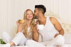 Le jeune café de boissons de couples se reposant dans le lit, homme hispanique de sourire heureux embrasse la femme Photographie stock libre de droits