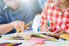 Le jeune campus d'étudiants aide l'ami rattrapant et apprenant Image stock