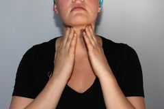 Le jeune cancéreux dans un foulard sent les ganglions lymphatiques dans son cou pour des morceaux image stock