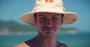 Le jeune Caucasien de portrait haut étroit de l'homme bel de brune dans le chapeau, regardant dans la caméra réfléchie, sourit so banque de vidéos
