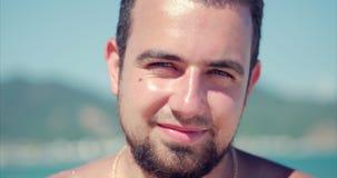 Le jeune Caucasien de portrait haut étroit de l'homme bel de brune une barbe, regardant dans la caméra réfléchie, sourit songeur, banque de vidéos